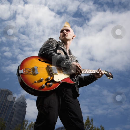Punk playing guitar. stock photo, Portrait of mid-adult Caucasian male punk holding guitar with skyline in background. by Iofoto Images