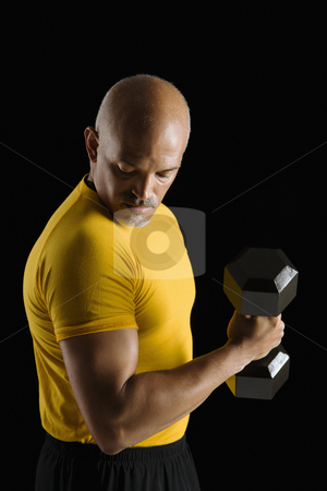 Man exercising with dumbbell. stock photo, Mid adult multiethnic man wearing yellow exercise shirt doing arm curls while looking at bicep. by Iofoto Images