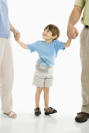 Boy with parents. stock photo, Boy holding hands with parents standing against white background. by Iofoto Images