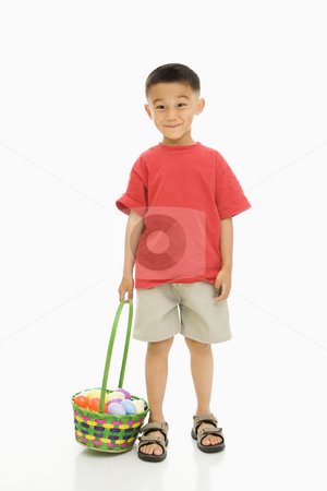 Boy with Easter basket. stock photo, Asian boy standing against white background holding Easter basket. by Iofoto Images