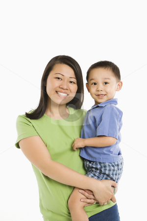 Mother holding son. stock photo, Asian mother holding son on hip smiling in front of white background. by Iofoto Images