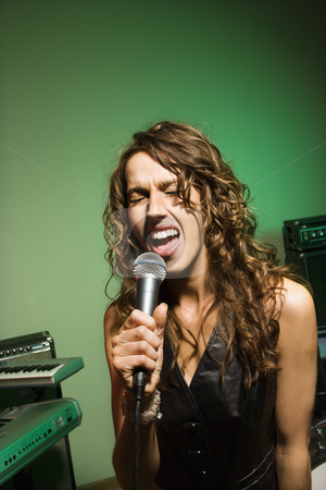 Female singing into mic. stock photo, Caucasian female singning into microphone. by Iofoto Images