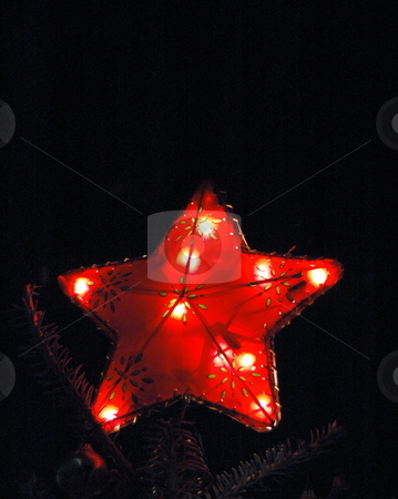 Christmas Tree Star Glows Red stock photo, Close up view of a Christmas Tree Star on top of a tree with Red lights. by Janie Mertz