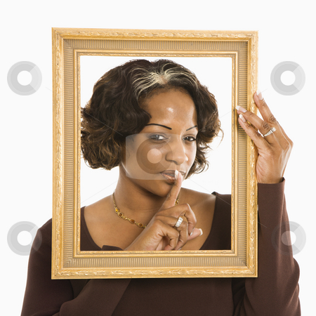 Woman quieting. stock photo, Woman holding frame around head holding finger up to lips. by Iofoto Images