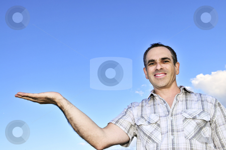 Happy man gesturing stock photo, Happy middle aged man gesturing on blue sky background by Elena Elisseeva