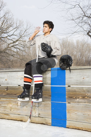 Hockey boy drinking water. stock photo, Boy in ice hockey uniform holding hockey stick sitting on sidelines drinking water. by Iofoto Images