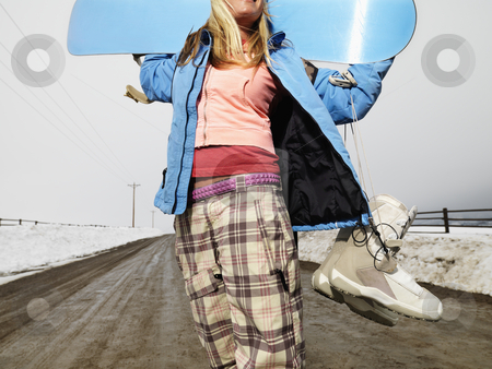 Woman holding snowboard. stock photo, Young woman in winter clothes standing on muddy dirt road holding snowboard and boots. by Iofoto Images