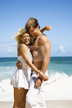 Happy smiling couple. stock photo, Couple embracing and smiling on Maui, Hawaii beach. by Iofoto Images