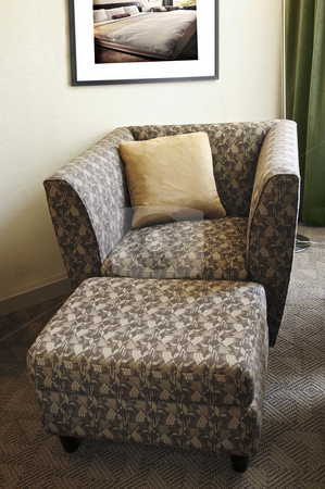 Armchair with ottoman stock photo, Comfortable armchair with cushion and ottoman. Photo on the wall is my own. by Elena Elisseeva