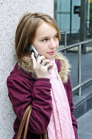 Teenage girl talking on cell phone stock photo, Teenage girl talking on cell phone outside by Elena Elisseeva