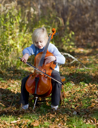Child Playing Cello stock photo, Child player her cello outside on an October afternoon. by John McLaird