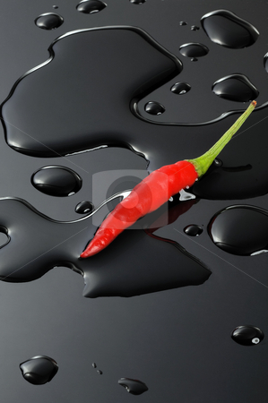 Red chili pepper stock photo, Red chili pepper on water drops over a black stone by Francesco Perre