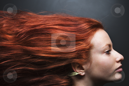Hair streaming behind woman. stock photo, Pretty redhead young woman profile with hair streaming out behind her. by Iofoto Images