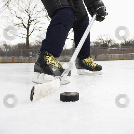 Boy playing ice hockey. stock photo, Boy in ice hockey uniform skating on ice rink moving puck. by Iofoto Images