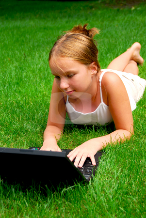 Girl computer grass stock photo, Young girl lying on grass in a park with laptop computer by Elena Elisseeva
