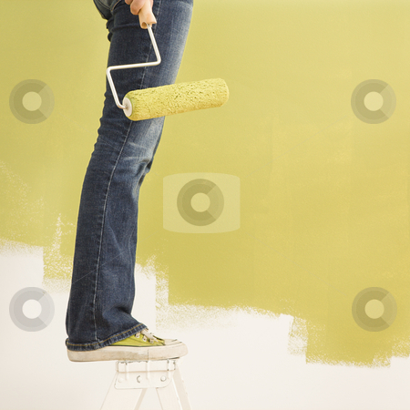 Woman painting. stock photo, Legs of woman standing on stepladder holding paint roller with painted wall. by Iofoto Images