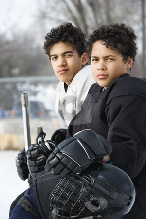 Boys in hockey uniforms. stock photo, Two boys in ice hockey uniforms sitting on ice rink sidelines looking. by Iofoto Images
