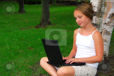 Girl computer stock photo, Young girl sitting in a park with laptop computer by Elena Elisseeva