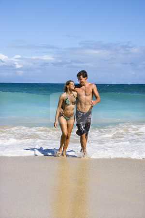 Couple on beach. stock photo, Attractive couple embracing and smiling as they walk out of water in Maui, Hawaii. by Iofoto Images