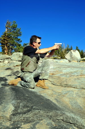 Target Shooting stock photo, Man target shooting in a kneeling position with a semi automatic pistol by Lynn Bendickson