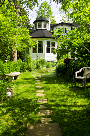 Home and garden stock photo, Path of steeping stones leading to a house in lush green garden by Elena Elisseeva