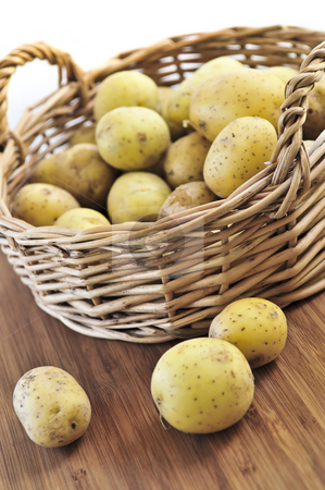 Row potatoes stock photo, Yellow raw potatoes in a basket close up by Elena Elisseeva