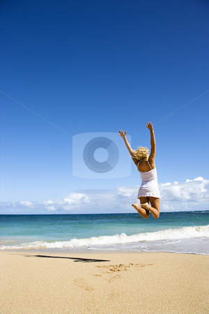 Woman jumping. stock photo, Pretty young woman jumping on Maui, Hawaii beach with arms raised into air. by Iofoto Images
