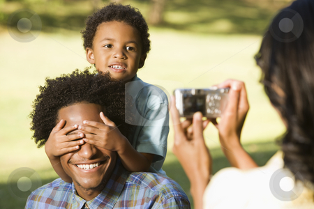 Woman taking picture. stock photo, Woman photographing husband and son in park with digital camera. by Iofoto Images