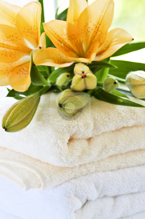 Stack of towels with flowers stock photo, Stack of soft luxury towels with fresh flowers by Elena Elisseeva