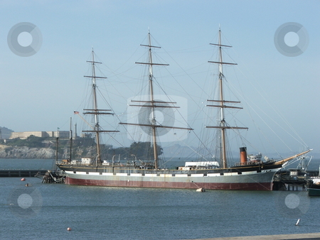The 1886 square-rigged ship Balclutha stock photo, The 1886 square rigger Balclutha is one of several ships displayed in the San Francisco Maritime National Historic Park located at the old Hyde Park Pier near Fisherman's Wharf.  The ship was built in Scotland and used to carry a variety of cargo around the world.  In the background is Alcatraz. by Dennis Thomsen