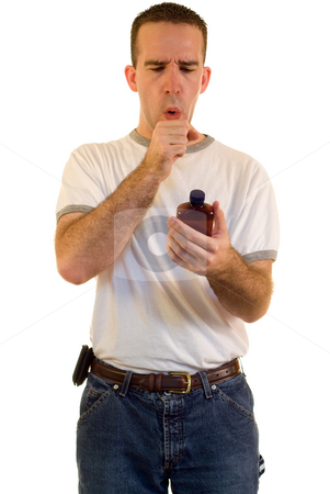Sick Man stock photo, A young man coughing from a cold, and holding medicine by Richard Nelson