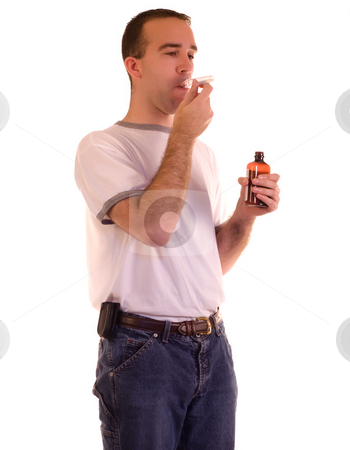 Man Swallowing Medicine stock photo, A young man swallowing some cough medicine by Richard Nelson