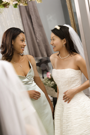 Bride and bridesmaid talking. stock photo, Asian bride and African-American bridesmaid talking to each other. by Iofoto Images