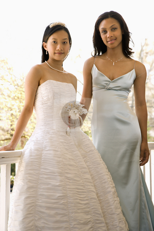 Portrait of bride and bridesmaid. stock photo, A portrait of a African-American maid of honor and Asian bride leaning against railing. by Iofoto Images