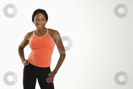 Woman with hand on hip. stock photo, African American young adult woman in athletic wear smiling at viewer with hands on hips. by Iofoto Images