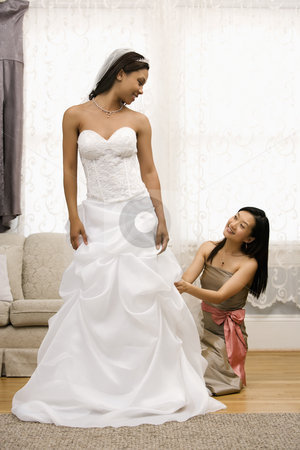 Bridesmaid adjusting bride's dress. stock photo, Asian bridesmaid fixing African-American bride's dress. by Iofoto Images
