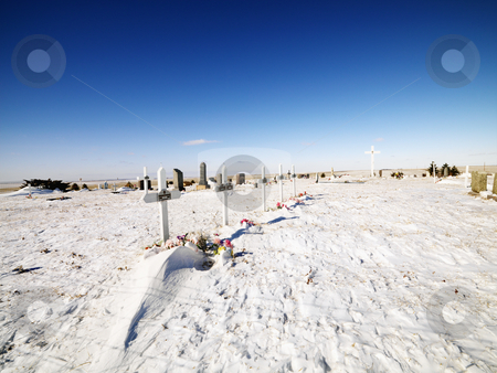 Snow covered graveyard. stock photo, Snow covered graveyard with clear blue sky in background. by Iofoto Images