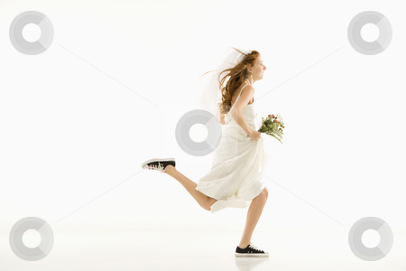 Running bride. stock photo, Caucasian bride running and holding bouquet. by Iofoto Images