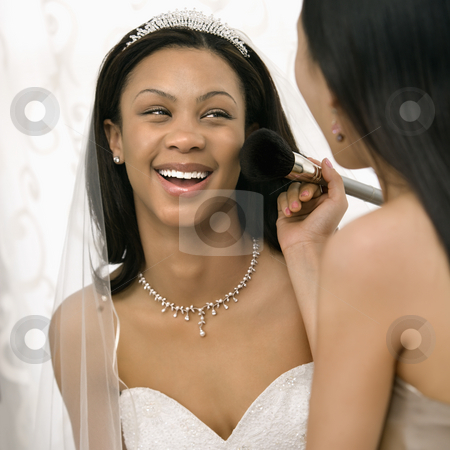 Bridesmaid applying makeup to bride. stock photo, Asian bridesmaid applying makeup to African-American bride. by Iofoto Images