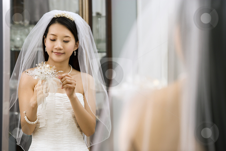 Bride looking at bouquet. stock photo, Asian bride looking at bouquet in mirror. by Iofoto Images