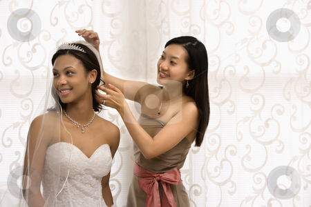 Bride and bridesmaid portrait. stock photo, Asian bridesmaid adjusting veil of African-American bride. by Iofoto Images