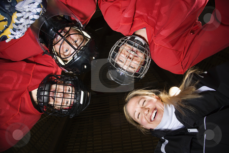 Women hockey player huddle. stock photo, Low angle of female hockey players in huddle with coach smiling. by Iofoto Images
