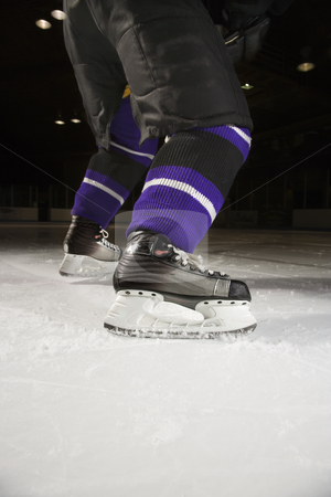 Ice hockey player. stock photo, Low angle of hockey player's legs and skates on ice rink. by Iofoto Images
