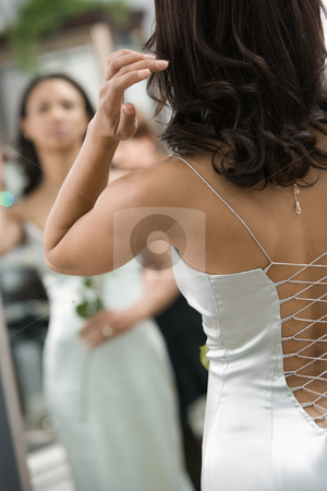 Back of woman in evenging gown. stock photo, Back of African-American woman in evening gown looking at mirror. by Iofoto Images