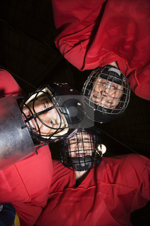 Women hockey player huddle. stock photo, Low angle of female hockey players in huddle smiling. by Iofoto Images