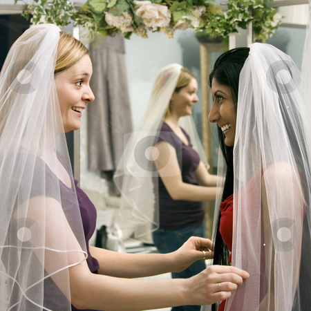 Friends trying on veils. stock photo, Indian woman and Caucasian woman trying on veils and looking in mirror. by Iofoto Images