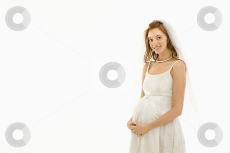 Pregnant bride. stock photo, Pregnant Caucasian bride with hands on her belly. by Iofoto Images