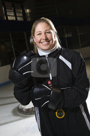 Female hockey coach. stock photo, Female hockey coach in uniform standing smiling. by Iofoto Images