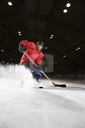 Woman playing hockey. stock photo, Caucasian woman hockey player sliding kicking up ice. by Iofoto Images
