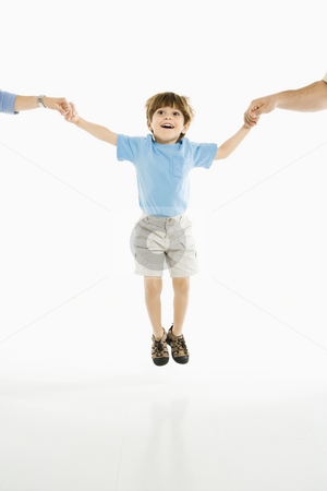 Boy jumping. stock photo, Boy jumping into air holding hands with parents against white background. by Iofoto Images